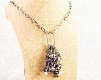 Long necklace. Cluster pendant, includes purple and clear glass faceted beads, metal beads and gun metal chain, all pulled together with gun metal coloured chain