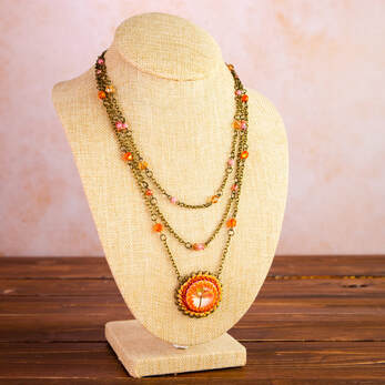 glass cabochon and woven with glass seed beads. Bronze metal chain and glass beads make up this three strand necklace